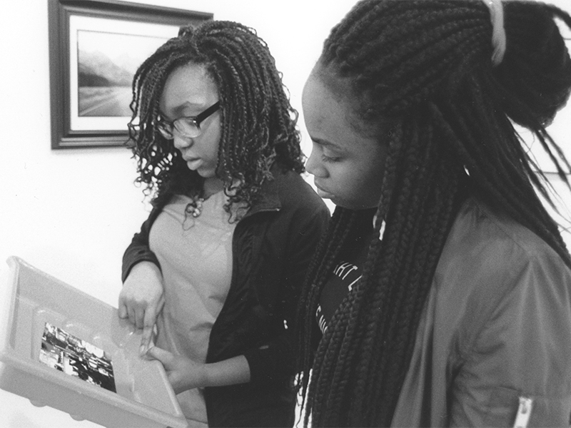 Two students examining their photograph from the darkroom